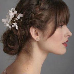 Coiffure de mariage chignon bas avec fleurs et frange